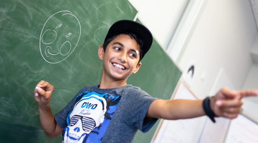 Kind steht an Tafel und zeigt in die Klasse