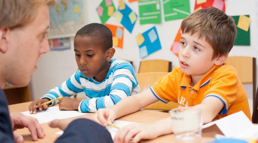 Lehrer erklärt etwas den Schülern, die Schüler sind aufmerksam